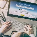 Consumer searching for flight options on laptop