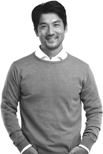 Photo of male professional in business casual shirt and sweater smiling with hands in pockets